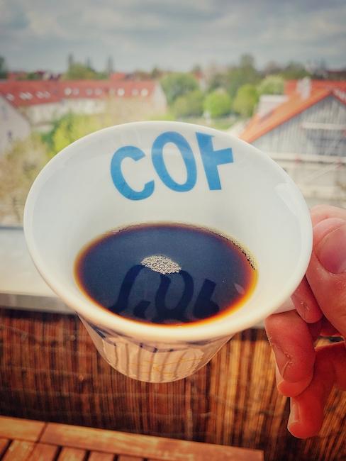 Eine weiße Kaffeetasse wird auf einem Balkon hochgehalten, so, dass der Betrachter hineinschauen kann. Das Bild ist aus der Egoperspektive aufgenommen und man erkennt schwarzen Filterkaffee, schätzungsweise ohne Zucker im Kaffee.
