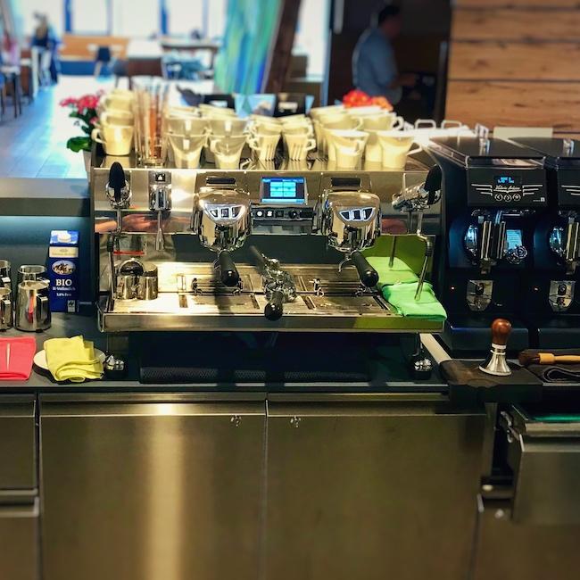 Man sieht eine ordentlich aufgebaute Kaffeebar aus der Barista Perspektive. Der Workflow ist hier von rechts nach links aufgebaut. Ganz rechts ist die Kasse, es folgen zwei Mythos One Kaffeemühlen, mit davor positionierter Tamperstation und Abschlagschublade, sowie einer Waage. Danach kommt eine Victoria Arduino Black Eagle mit zwei Brühgruppen in mattschwarz und silber. Rechts von ihr ist die Milchposition sowie die Ausgabe zu erkennen. An den jeweils wichtigen Punkten sind farbig unterschiedliche Lappen verteilt. Alles ist gut erreichbar. Ein sehr durchdachter Baraufbau.