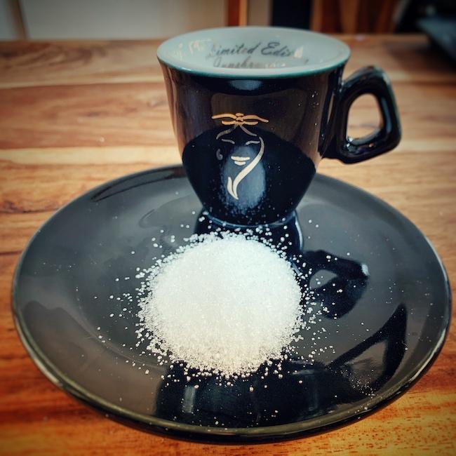 Ein Haufen Zucker vor einer schwarzen Varesina Espresso Tasse, auf einem Holztisch. Beides steht auf einer schwarzen Untertasse. Soviel Zucker wie hier, etwa 10g, landen etwa in den meisten Getränken, wenn Zucker im Kaffee genutzt wird.