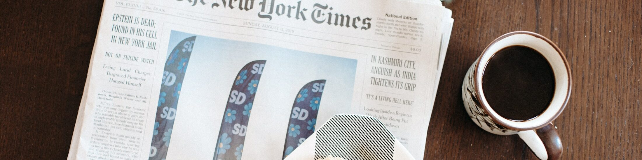 Man sieht die Szene aus der Vogelperspektive. Eine Zeitung der New York Times liegt auf einem Holztisch. Daneben steht eine Tasse schwarzer Kaffee. Am unteren Bildrand erkennt man noch etwas Gebäck auf einem Teller. Ein Sinnbild für eine Eilmeldung, oder Extrablatt, bezüglich des einfach mal Kaffee Steady Launches