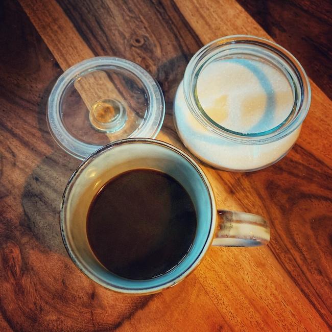 Eine Tasse Kaffee und eine Zuckerdose stehen auf einem dunklen Holztisch. Die Szene ist von schräg oben aufgenommen. Unten links im Bild steht die graue Tasse, etwa halb gefüllt mit Kaffee. Oben rechts im Eck sieht man die gläserne Zuckerdose, deren Deckel geöffnet ist und neben ihr liegt.