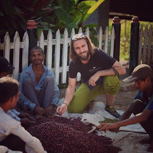 Thomas von Bean United bei einem Besuch auf einer Kaffee Farm. Kommunikation vor Ort ist wichtig, wenn man wirklich Gutes tun will mit Kaffee. Man sieht hier Thomas lächelnd zwischen vier Arbeitern sitzen, die gerade gepflückte Kaffeekirschen aussortieren. Dabei setzten sie auf einer weißen Plastik Plane vor einem weißen Gartenzaun und schauen alle entspannt.