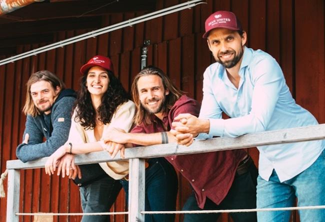 Wir sehen das gut gelaunte Team von Bean United. Ganz rechts Thomas und Philipp Greulich. Alle vier schauen fröhlich in die Kamera, während sie nach vorne an einem Geländer lehnen. Das Ziel von Bean United ist mit Kaffeehandel Gutes tun. Eine Social Coffee Company