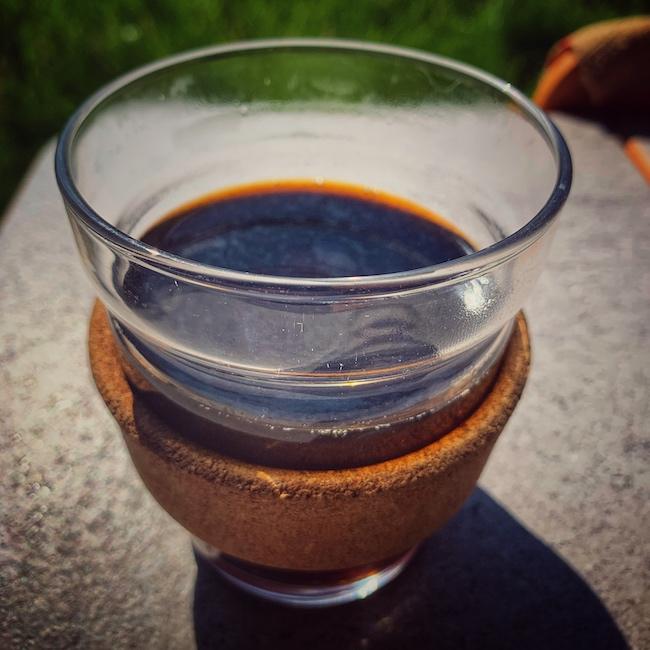 Ein Keep Cup Mehrwegbecher als Alternative zu Einwegbechern. Dieser hier steht auf einem Tisch, im Hintergrund erkennt man sehr unscharf eine Wiese. Der Becher ist in der Nahaufnahme zu sehen und mit schwarzem Filterkaffee gefüllt. Dieses Modell ist aus ein Glas Mehrwegbecher für Coffee To Go und hat einen Korkkragen.
