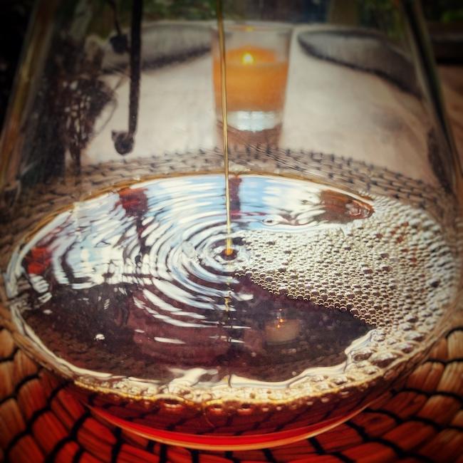 In Nahaufnahme sehen wir wie Filterkaffee in den Bauch der Chemex Filterkaffeekanne gebrüht wird. Er hat eine hellbraune Farbe, die eher wie dünner Kaffee wirkt. Das kann aber täuschen. Im Hintergrund sieht man eine Kerze stehen.