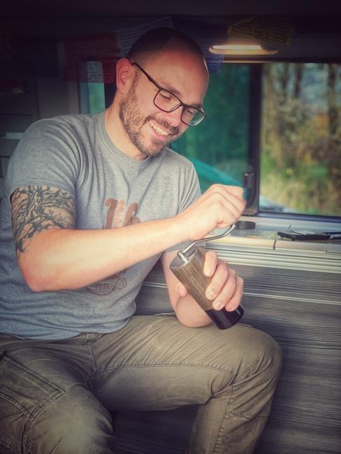 Horst von einfach mal Kaffee beim Kaffee machen im Camper. Er sitzt in einem Campern und mahlt mit der Handmühle frisch den Kaffee. Man sieht, dass es ihm spaß macht.
