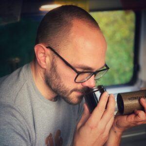 Horst von einfach mal Kaffee sitzt in seinem Camper Van und riecht genussvoll an frisch gemahlenem Kaffee. Riechen ist der wichtigste Teil unserer Kaffee Sensorik, zu erlernen auch in einem Sensorik Kurs.