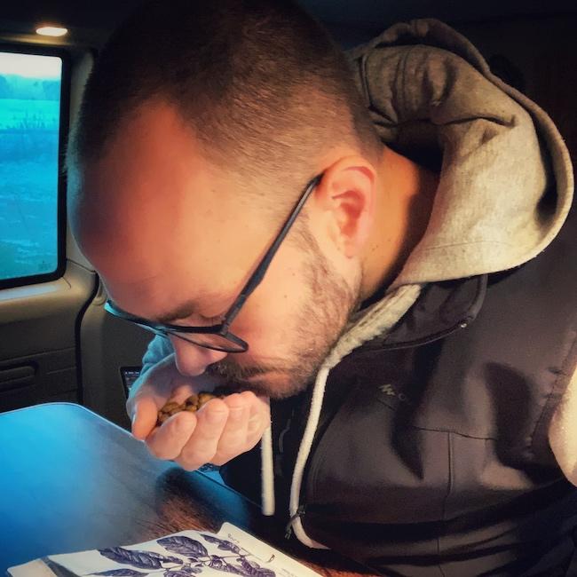 Horst sitzt in seinem Camper Van und riecht konzentriert an einer Handvoll Kaffeebohnen. Man sieht das er Kaffeegenuss mit allen Sinnen betreibt. Er trägt eine schwarze Wanderweste über einem grauen Kapuzenpulli und eine Brille.