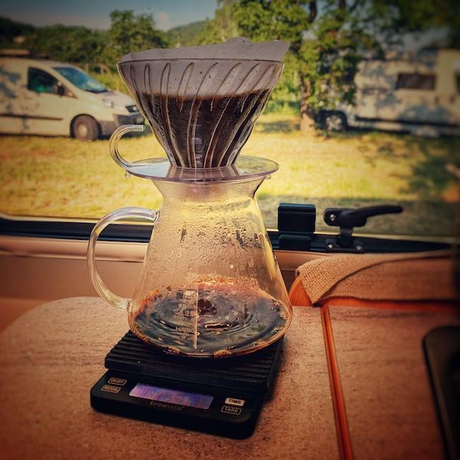 Auf der Küchenzeile in einem Kastenwagen Campern steht ein Hario V60 Glas Brewing Kit auf einer Brewista Smart Scale Kaffeewaage. Gerade läuft feinster Filterkaffee durch und sammelt sich in der Glaskanne. Im Hintergrund schaut man aus dem Küchenfenster auf eine Obstwiese auf der noch zwei weiter Campervans zu erkennen sind. Die Sonne scheint.