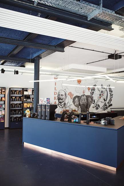 Die Showrösterei der Kaffeerösterei Wildkaffee in Garmisch Patenkirchen in der Bahnhofstraße. 8 Ein sehr vorderer Raum. Auf dem Bild sieht man die Barista Bar mit matt blauem Dekor. Darauf stehen drei Mythos One Kaffee Mühlen, in die Bar eingebaut ist eine Mod Bar Espresso Maschine. Hinter der Bar sieht man ein gefülltes Warenregal, sowie eine Wandmalerei.