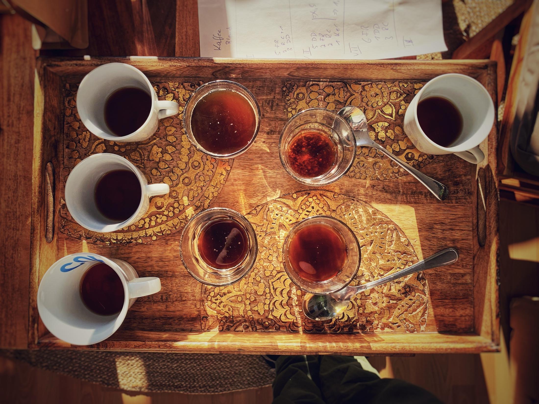 Auch zuhause kann man Kaffee verkosten. Das Vergleichende trinken ist förderlich für den eigenen Kaffeegenuss. Aus der Vogelperspektive sieht man hier ein Holztablet mit goldenen Verziehrungen. Darauf stehen unterschiedliche Gläser und Tassen gefüllt mit schwarzem Filterkaffee, sowie einige Cuppinglöffel.