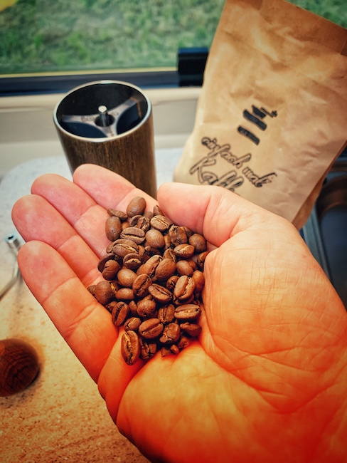 Eine Handvoll einfach mal Kaffee Filterkaffee Kaffeebohnen aus der Egoperspektive. Auf dem Tisch im Hintergrund steht eine Comandante Kaffeemühle, sowie eine Tüte einfach mal Kaffee Filterkaffee.