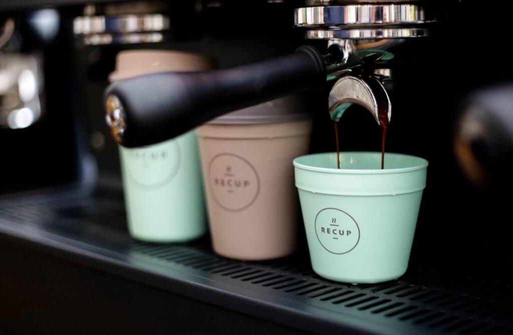 Auf einer schwarzen Espressomaschine stehen die drei Größen der ReCup Pfandbecher für Coffee To Go. Der kleinste mit ca. 200ml Fassungsvermögen wird gerade mit aus einem doppelten Siebträger mit dunkelbraunem Espresso gefüllt. Er und der größte Becher mit ca. 500ml Fassungsvermögen sind in typischen Mintgrün. Der Mittlere Mehrwegbecher für Cappuccino ist im ReCup braun.