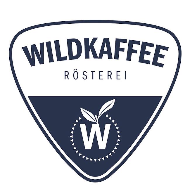 """Das Logo der Kaffeerösterei Wildkaffee aus Garmisch Patenkirchen. Dreieckig mit abgerundeten Ecken. Im Oberen Teil steht der Schriftzug Wildkaffee, darunter: """"Rösterei"""". In der unteren Hälfte ist die Spitze blau ausgefüllt mit einem weißen """"W"""" aus dem zwei Blätter einer Kaffeepflanze wachsen. Das """"W"""" ist kreisförmig umrandet mit weißen Punkten."""