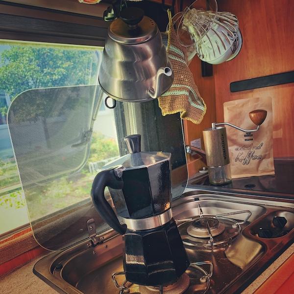 Wie macht man Kaffee im Camper? ganz viele Menschen nutzen eine Bialetti Herdkanne. Hier sehen wir in einem Camper Van eine Bialetti Kanne auf dem Gasherd stehen. Sie ist schwarz, die Einrichtung aus Holz. Im Hintergrund erkennen wir weitere Kaffeeausrüstung, sowie ein Päckchen einfach mal Kaffee Blend.