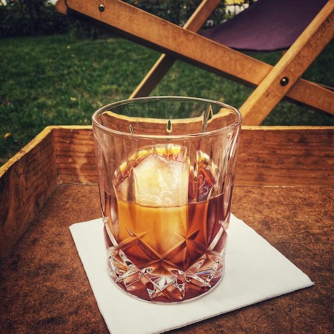 Ein Cold Brew in einem schön verzierten Glas. Wir sehen das Glas mit der rubinbraunen Flüssigkeit auf einer weißen Serviette auf einem braunen Holztablett stehen. Im Glas schwimmt ein großer Eiswürfel. Im Hintergrund erkennt man verschwommen einen hölzernen Liegestuhl, auf einer Wiese.