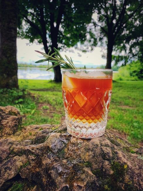 Ein Espresso Tonic, ein sehr modernes Sommer Kaffee Rezept mit tollen Aromen, ein echt erfrischender Genuss. Hier steht ein Glas davon auf einem mit Moosen bewachsenen Stein. Im unscharfen Hintergrund erkennt man eine Wiese ein paar Bäume und das Ufer eines Sees. Das Getränk selbst ist in einem schön verzierten Kristallglas, oder Whiskey Tumbler. Ein guter Espresso Tonic wie dieser hier hat zwei Phasen. Unten das transparente Tonic Water und darüber eine Rubin braun Farben Schicht Espresso. In dem Glas schwimmen drei Eiswürfel und ein Rosmarin Zweig.