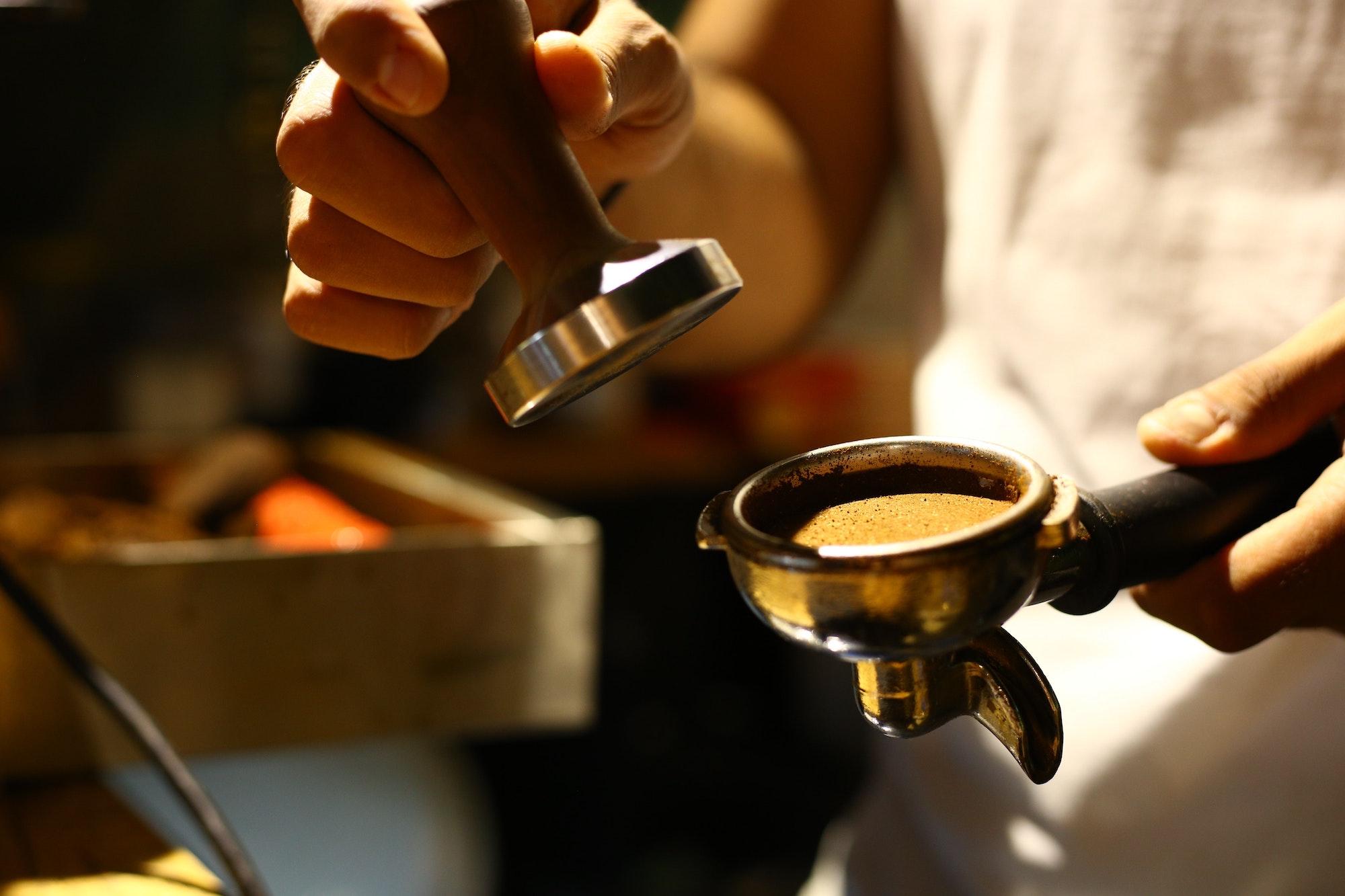 In Nahaufnahme sehen wir einen Siebträger gefüllt mit Espresso Mehl, sowie einen Tamper. Beides wird von einem Unbekannten in der Hand gehalten. Er trägt ein weißes Oberteil.