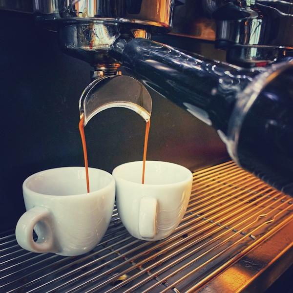 Zwei Espresso Tassen stehen auf einer Maschine, während hellbraune Flüssigkeit aus einem Siebträger hineinläuft. Die Espressomaschine im Hintergrund ist schwarz, genau wie der Griff des Siebträgers.