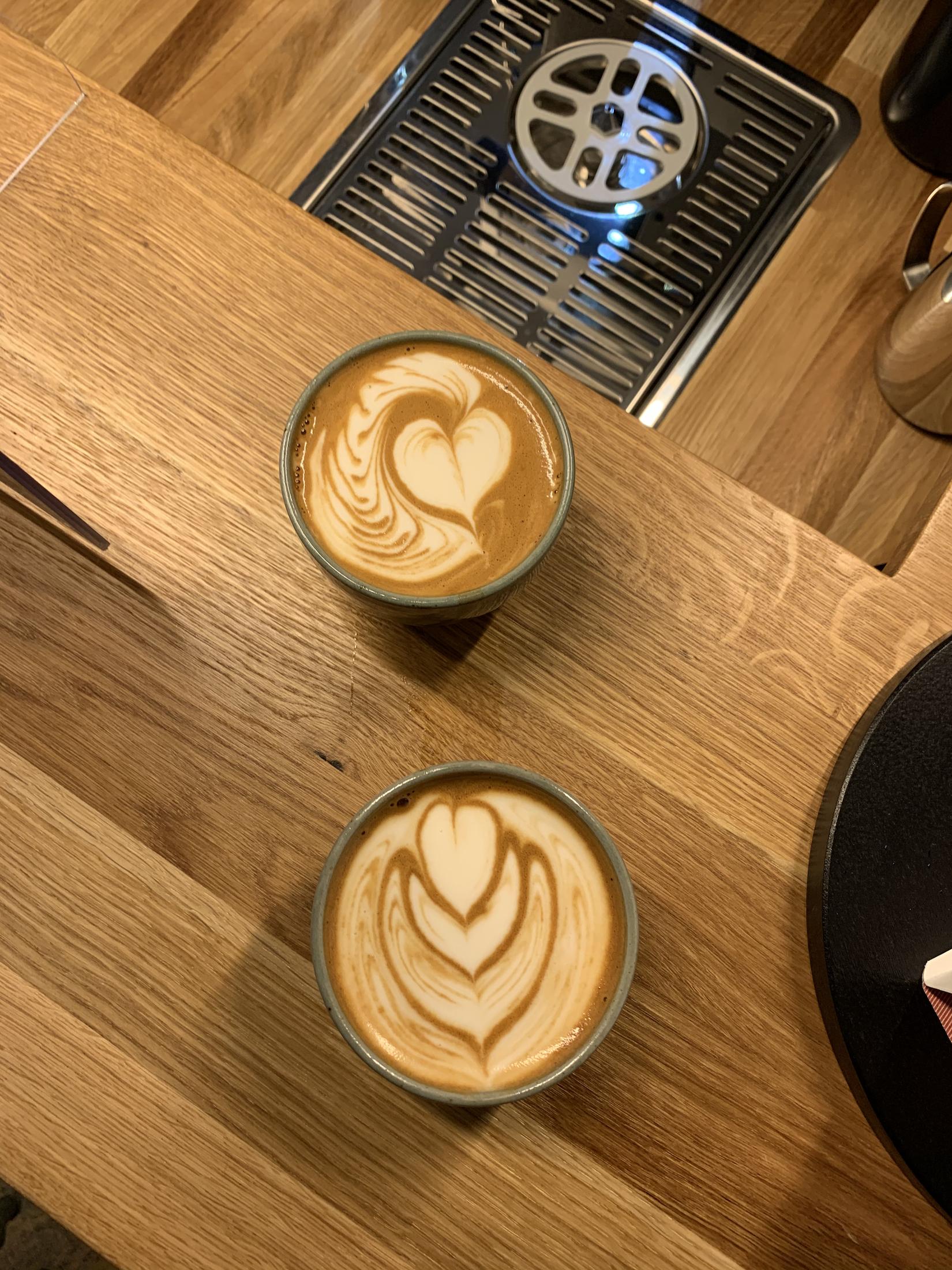 Latte Art mit Milchersatzprodukten, gegossen von Barista Christian Ullrich. Aus der Vogelperspektive sehen wir zwei grüne Tontassen, gefüllt mit Milch und Kaffee. Auf der einen Tasse ist ein Weaveheard zu sehen, auf der anderen eine Tulpe. Sie stehen auf einer Holztheke mit verschiedener Helligkeit.