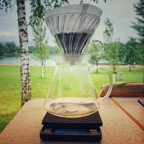 Es gibt viele Wege guten Kaffee im Camper zu machen. Hier sehen wir einen Hario V60 Filter in der Küche eines Vans. Es wird gerade Kaffee darin gebrüht. Im Hintergrund viel Grün, eine Buche und ein See.