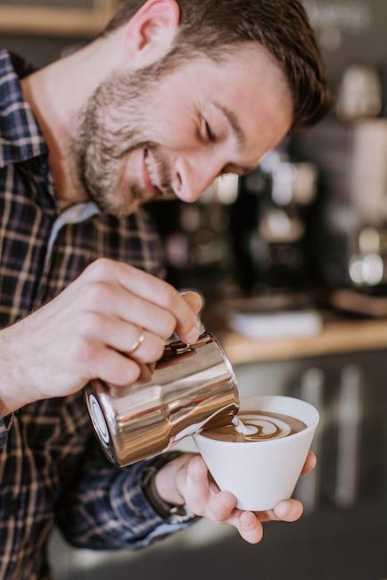 """Immer lächelnd bei der Arbeit, solange es um Kaffee geht. Christian Ullrich trinkt zwar selten Milch im Kaffee, gießt sie aber sehr kunstvoll ein. Hier gibt er uns Tipps, wie auch wir den perfekten Milchschaum selber machen können. Im Bild trägt er ein Kariertes Hemd lächelt und gießt das Latte Art Motiv """"Tulpe"""" in eine weiße Tasse."""