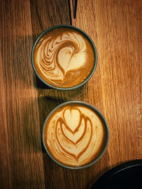 Zwei Tassen mit Latte Art Motiven stehen auf einer Holzbar. Milch im Kaffee kann sehr dekorierend wirken, wenn sie wie hier kunstvoll eingeschränkt wurde. Künstler hier war Barista Christian Ullrich.