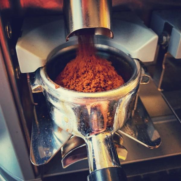 Ein Siebträger wird an der Espressomühle mit Kaffeemehl gefüllt. Alles aus glänzendem Edelstahl. Korrektes Mahlen ist ein wichtiger Schritt um einen Espresso gut zubereiten zu können.