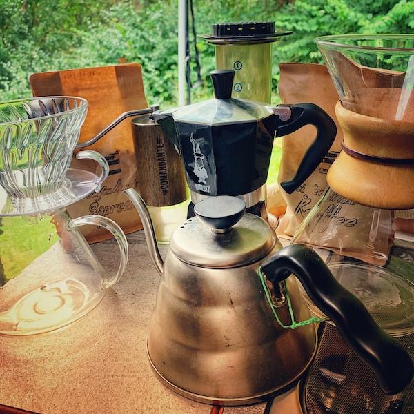 Viele verschiedene Wege, um einen Kaffee zu extrahieren stehen auf einem Tisch. Im Hintergrund sieht man grüne Natur. Auf dem Tisch steht ein Hario V60 Glassfilter, eine Chemex, eine AeroPress, eine Bialetti, ein Buono Drip Kettle und zwei Packungen Kaffee. Aber was ist die beste Art Kaffee zu kochen?