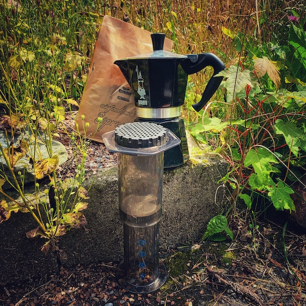 Eine Bialetti, eine AeroPress und eine Tüte Kaffee in hohem Gras. Wie macht man Kaffee richtig?