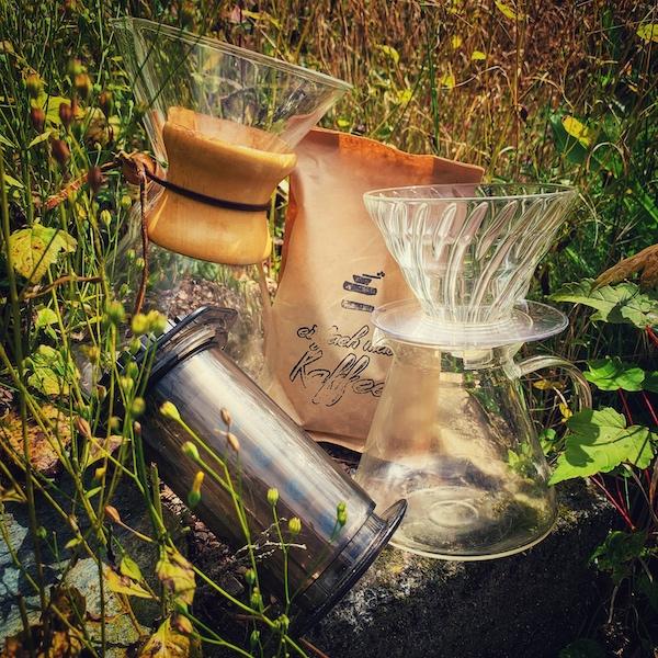 Ein Hario V60 Glas Brewing Kit, eine Aeropress, eine Cremes und eine Tüte Kaffee in hohem Gras. Wie macht man Kaffee eigentlich richtig?