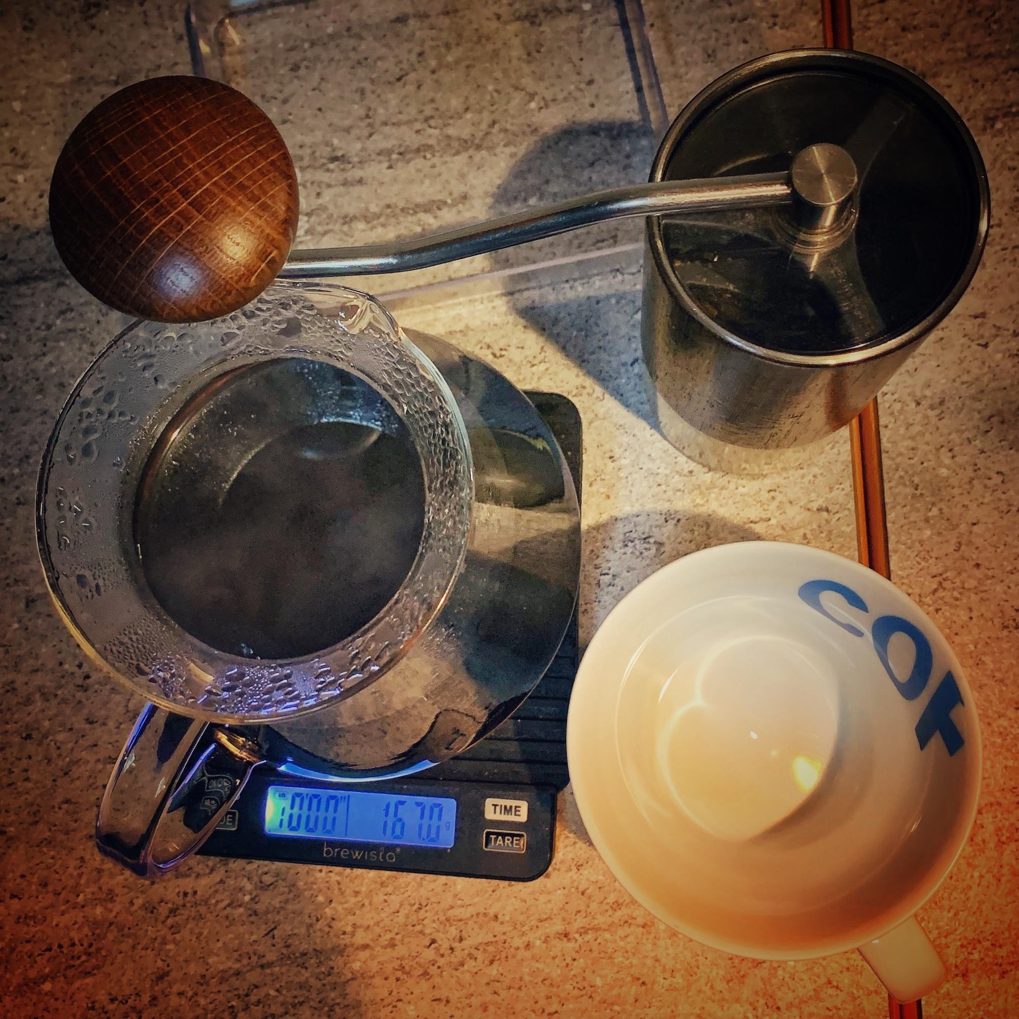 Aus der Vogelperspektive sehen wir eine Commandante Kaffeemühle, eine weiße Porzellantasse, ein Hario Glas Kanne und eine Brewista Smart Scale auf einem grau melierten Tisch stehen.