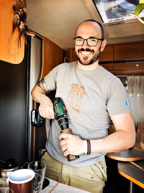 Horst steht in seinem Van und lacht in die Kamera, während er mit seinem Akkuschrauber Kaffee mahlt. Er trägt ein graues Shirt und eine Brille.