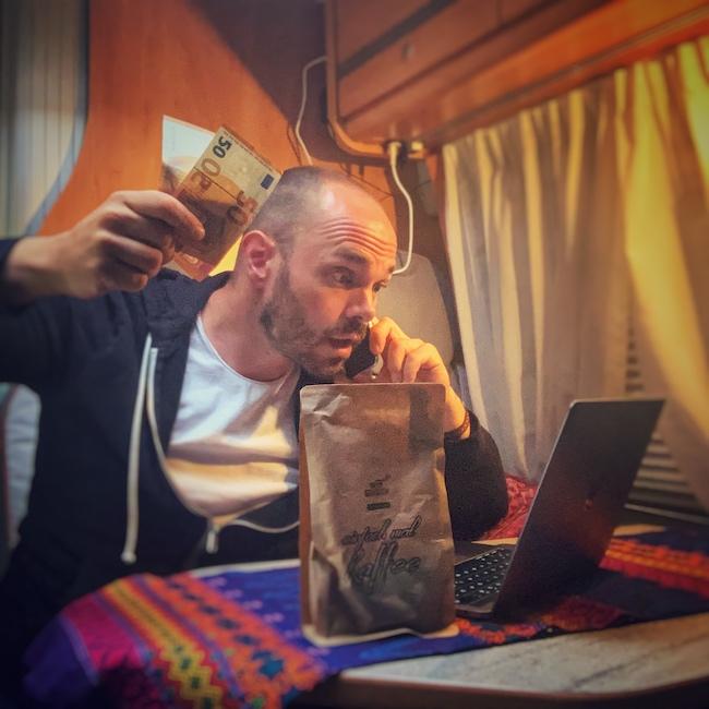 Horst von einfach mal Kaffee in seinem Van, hält zwei fünfzig Euro Scheine in der Hand, telefoniert mit der anderen und schaut aufgeregt auf seinen Laptop. Im Vordergrund steht eine Packung nachhaltiger Kaffee.