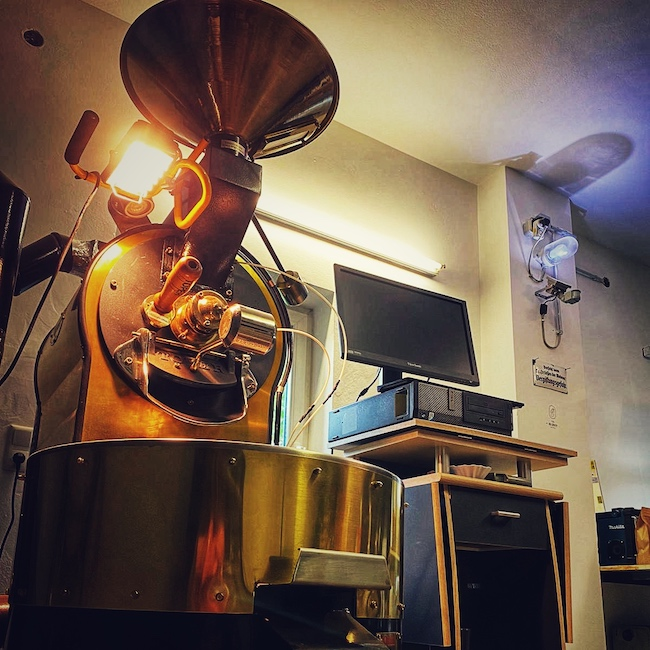 Eine gold schwarze Röstmaschine in einer Rösterei. Der Raum ist schön ausgeleuchtet und wir sehen von unten links auf die golden glänzende Röstmaschine von Toper. Gerade ist sie nicht im Einsatz.