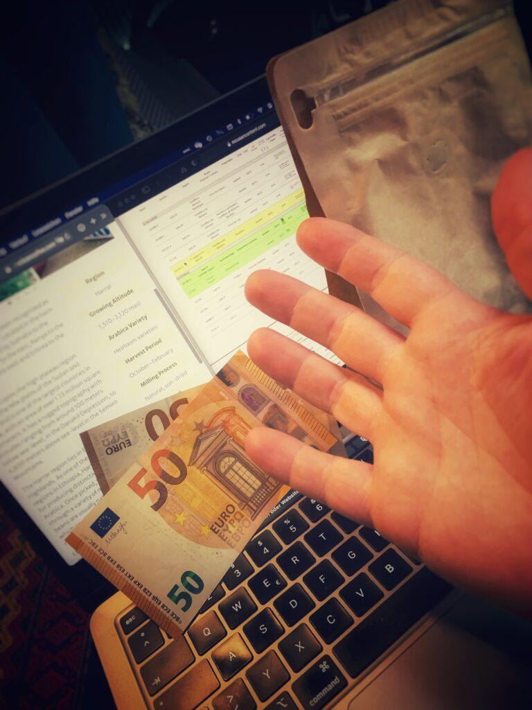 Kaffeehandel weltweit läuft inzwischen vor allem über Handelsportale. Davon sehen wir hier zwei auf dem Bildschirm eines Laptops. Davor liegen zweii fünfzig Euro Scheine.