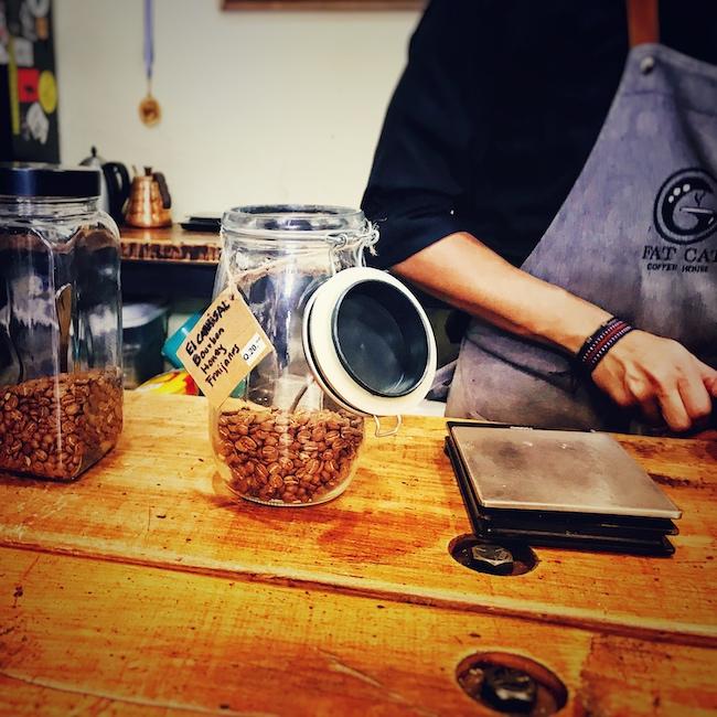 Ein offenes Weckglas mit Kaffee steht auf einer Holztheke, neben einer Kaffeewaage. Hinter der Bar arbeitet ein Barista, den man im Anschnitt ab der Schulter sieht.