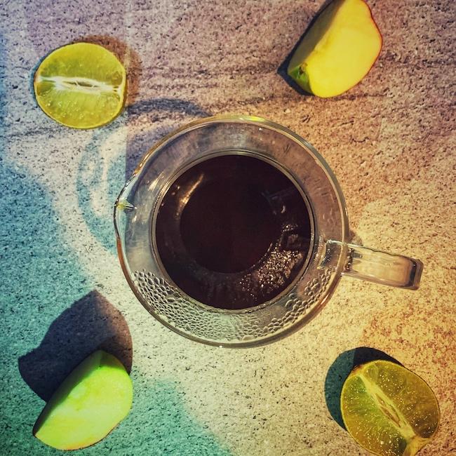 Um eine gläserne Kaffeekanne, gefüllt mit Filterkaffee, liegt aufgeschnittenes Obst. Sinnbild für Fruchtsäuren im Kaffee. Nicht der einzige Grund für sauren Kaffee.
