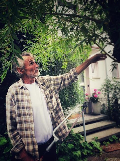 Der Interviewgast des Tages, steht mit kariertem Hemd in seinem Garten und erklärt etwas an einem Baum. Man merkt, dass er für Agroforstwirtschaft und Entwicklungshilfe brennt.