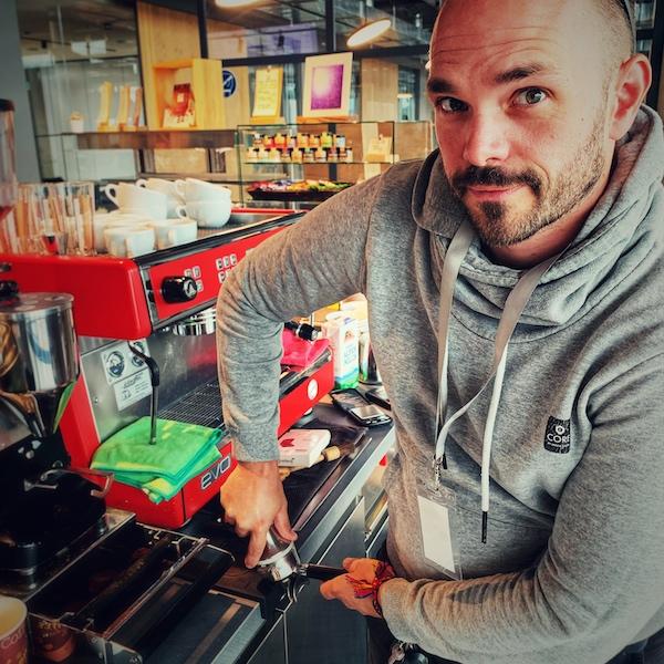 Horst von einfach mal Kaffee steht an einer Barista Bar und Tampt. Er trägt einen grauen Kapuzenpulli und schaut erwartungsvoll in die Kamera. Im Hintergrund sieht man eine rote Dalla Corte Espressomaschine, sowie eine unscharf weitere Dekoration