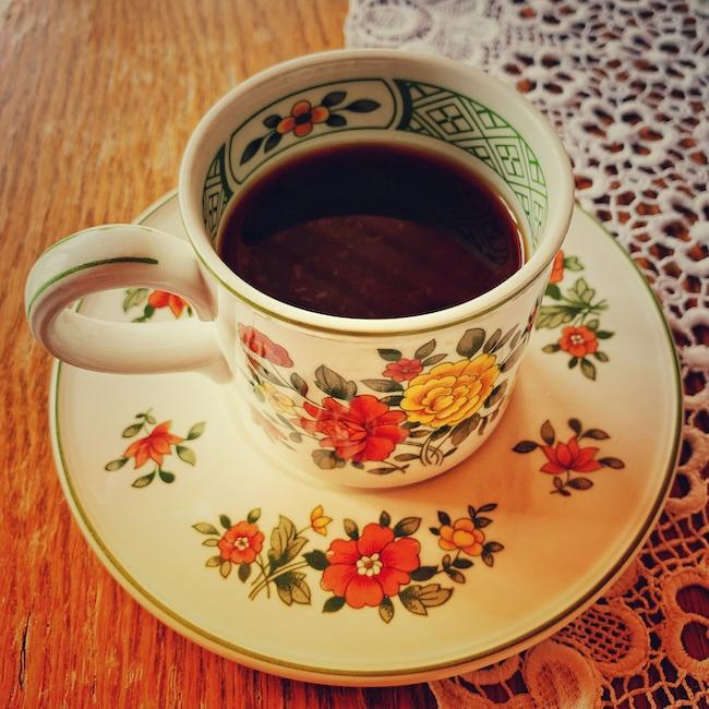 Eine weiße Kaffeetasse mit buntem Blümchenmuster auf einer passenden Untertasse, auf einem Holztisch mit weißem Spitzendeckchen.