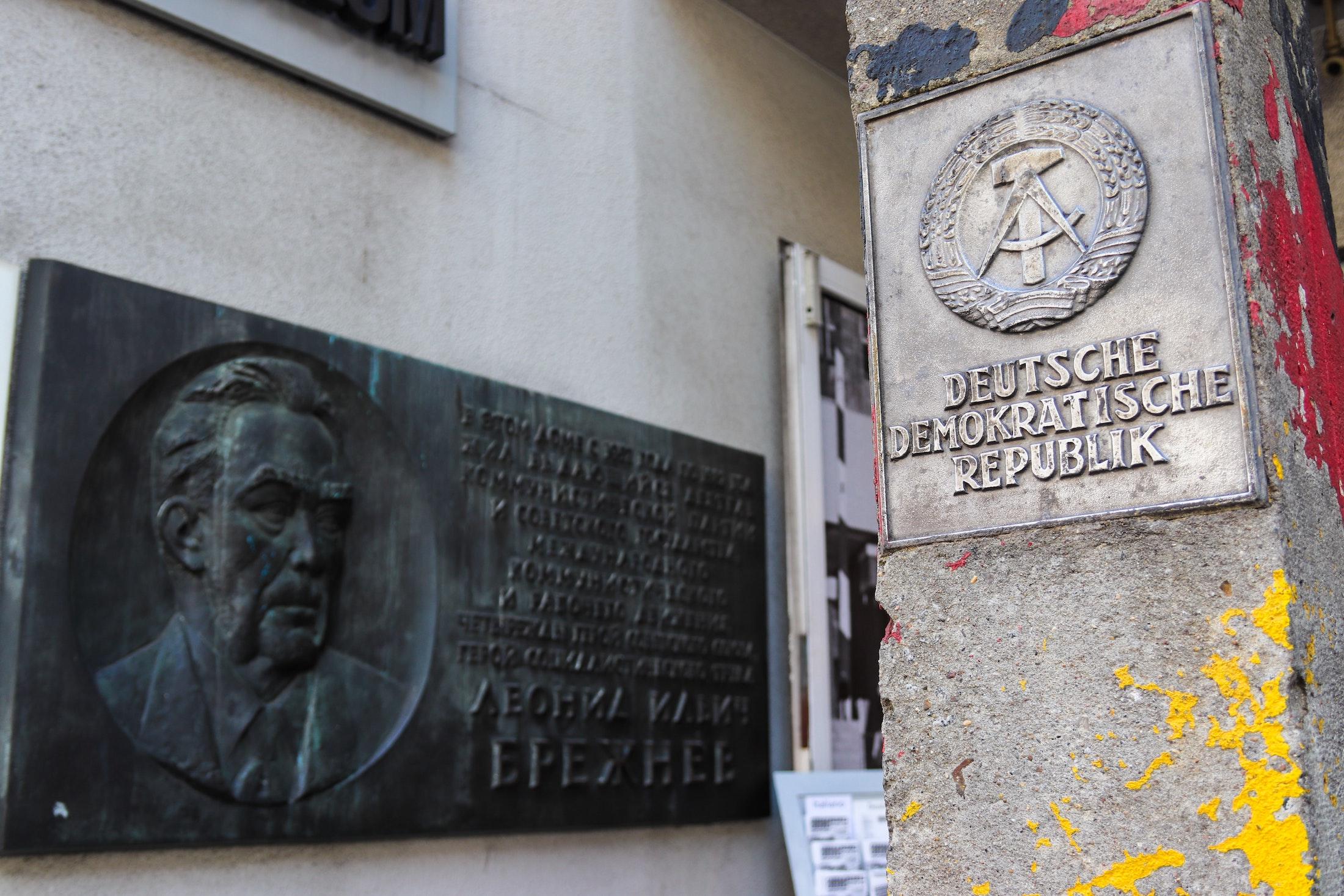 Eine Szene aus Berlin, mit dem Hoheitsschild der DDR an einem Betonpfeiler