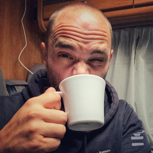 Horst trinkt aus einer weißen Kaffeetasse, während er in seinem Van sitzt. Es ist wohl saurer Kaffee, denn er verzieht das Gesicht. Oder hat er Magenschmerzen?