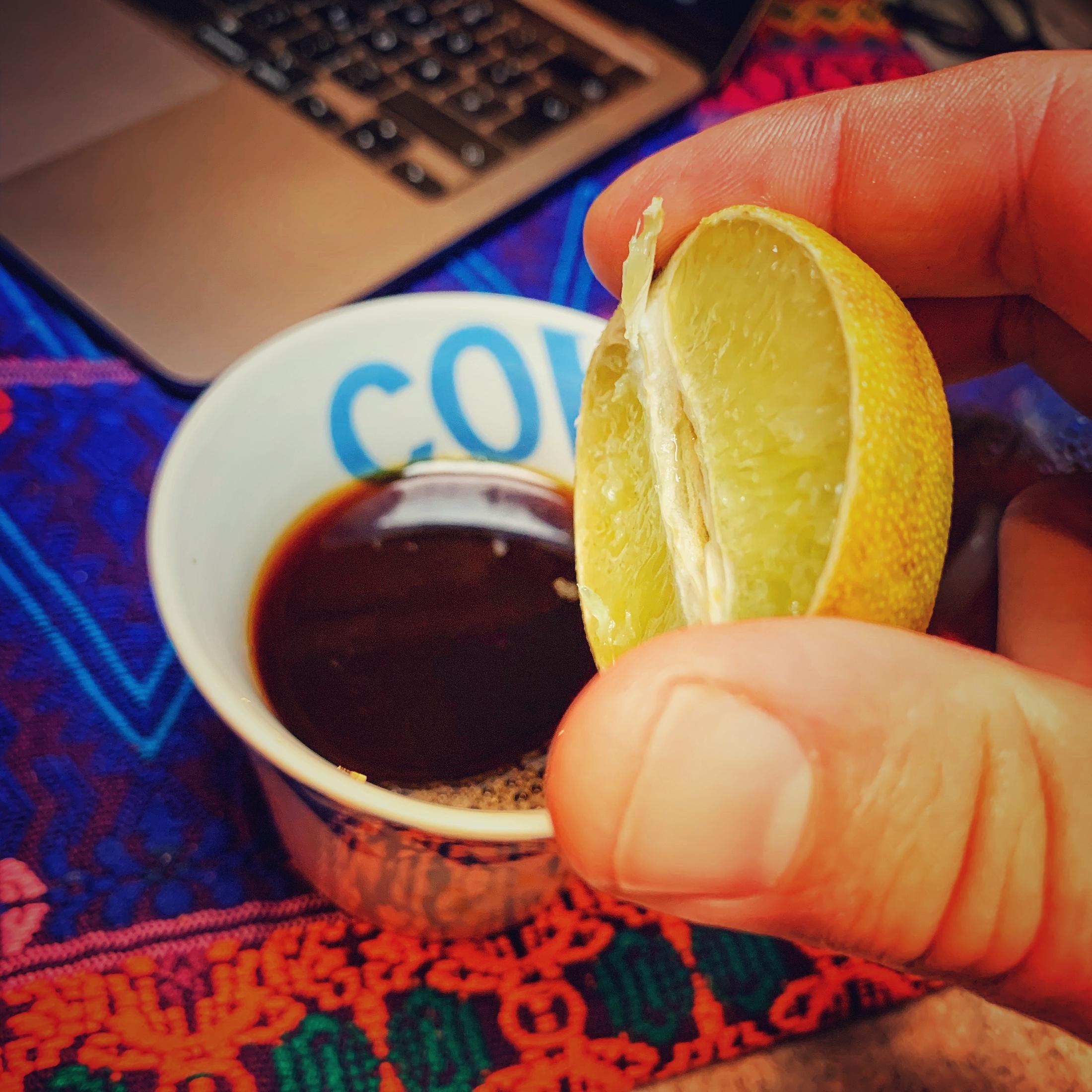 Eine Tasse Kaffee neben einem Laptop auf einer bunten Tischdecke. Darüber wird eine halbe Limette gehalten. Sinnbildlich für Säure im Kaffee