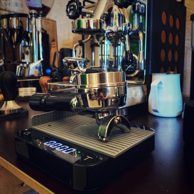 Ein Siebträger einer Rocket Espressomaschine steht auf einer Acaia Luna Kaffee Waage. Im Hintergrund sieht man die Maschine, sowie eine Mühle und Zubehör stehen. Alles samt ist nah aufgenommen und befindet sich auf einer schwarzen Barista Bar.