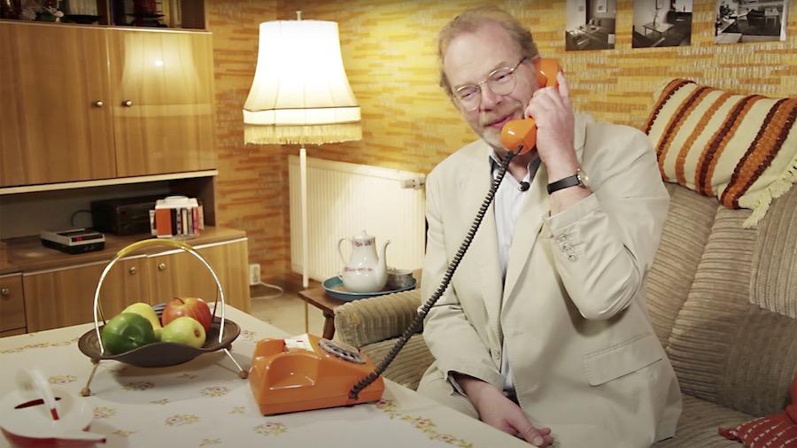 Frag Dr Wolle Titelbild. Er sitzt in einem beigen Anzug in einem klassisch im DDR Stil eingerichteten Wohnzimmer und telefoniert über ein orangenes Telefon.