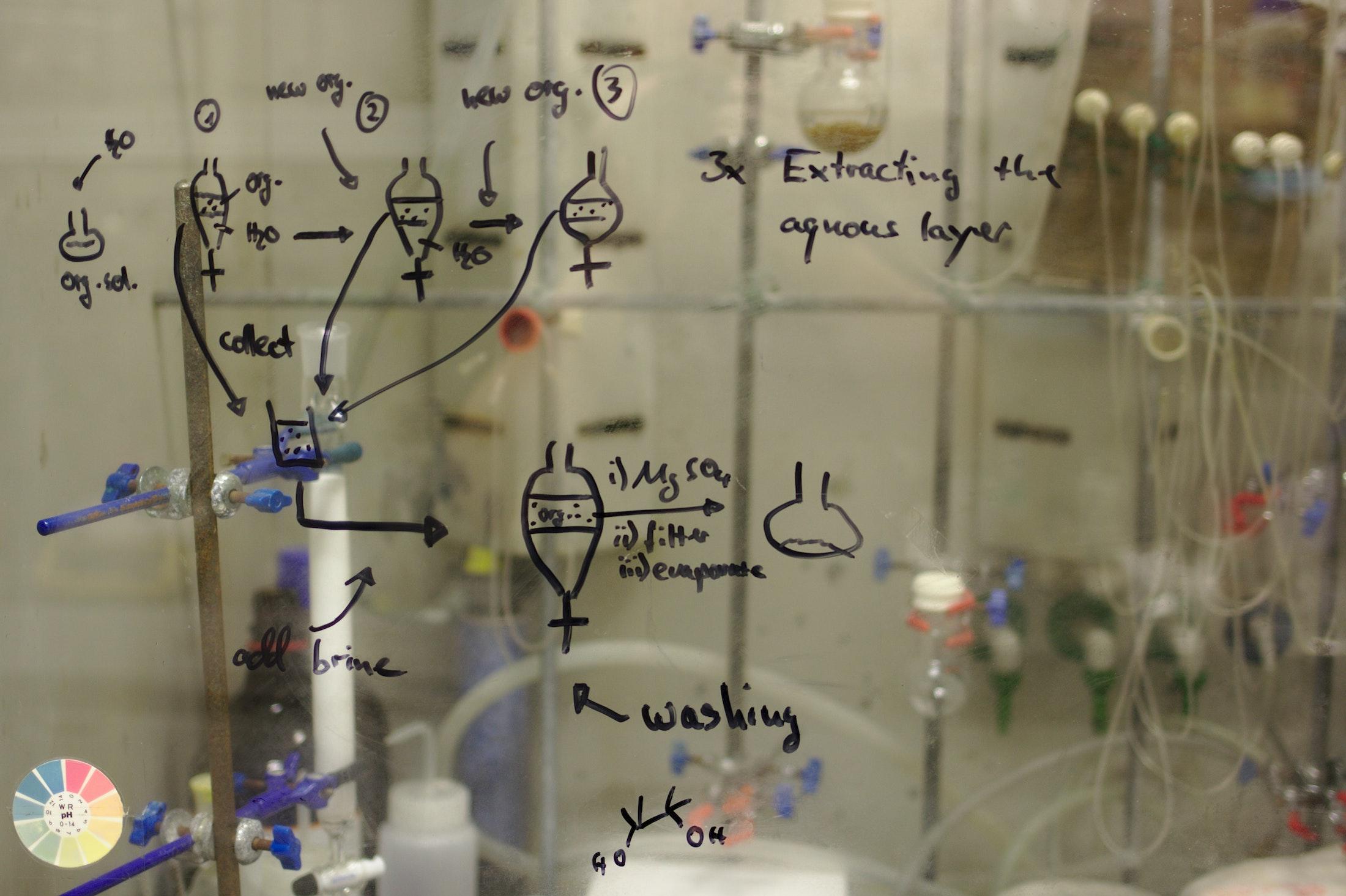 Chemische Formeln an einer Glaswand, verschwommen sieht man das Labor dahinter