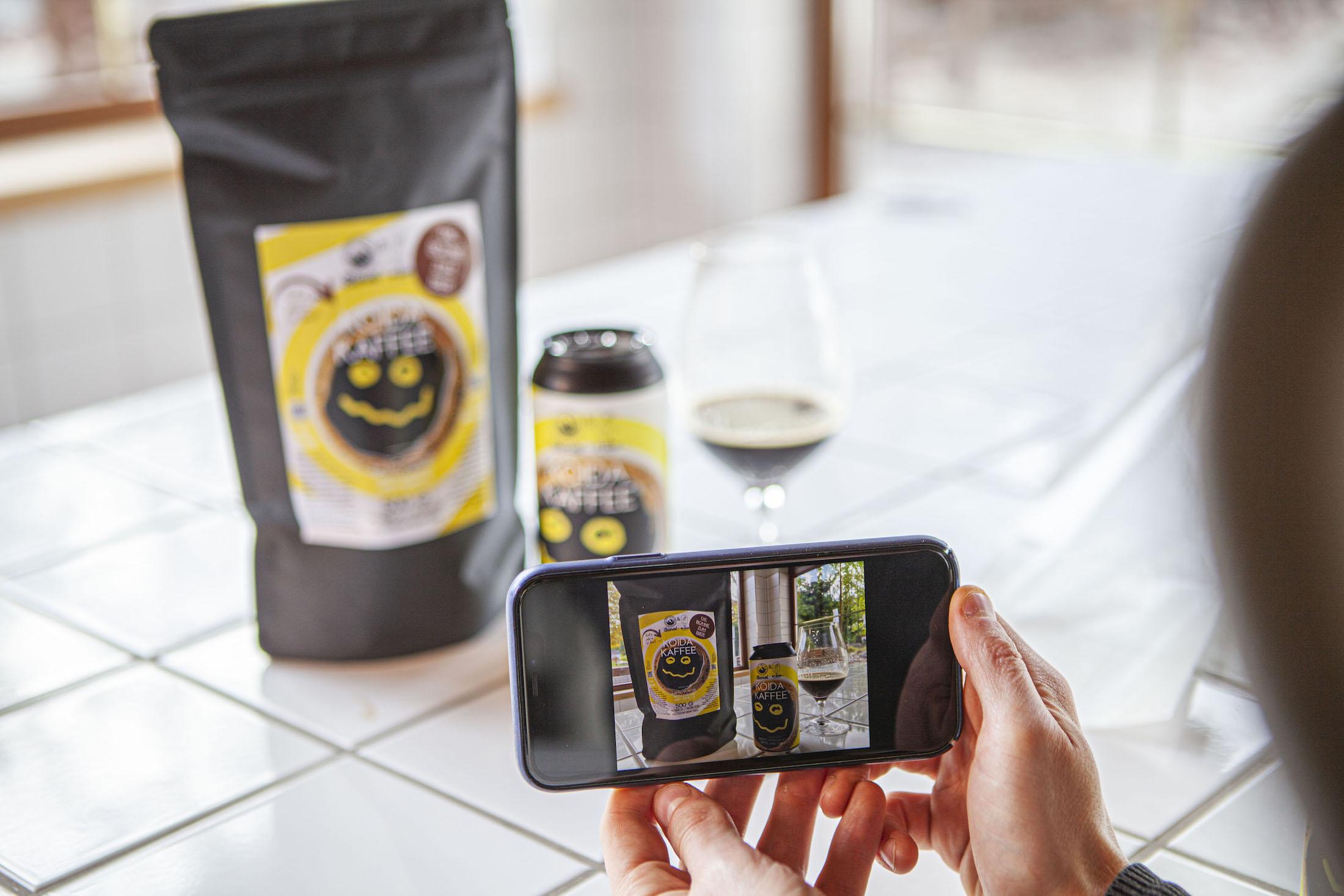 Das Kaffee Bier von Bierol steht in einer Dose auf einem Fliesentisch. Davor steht ein Glas mit einem Schluck Craft Bier, dahinter steht der Kaffee in Packung