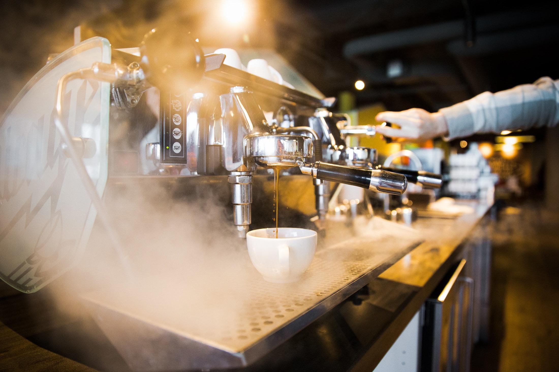 Eine silberne Siebträgermaschine steht auf der Bar und in ihrem eigenen Dampf. Der Barista an dieser Kaffee Bar hält einen Hebel auf der anderen Seite gedrückt.