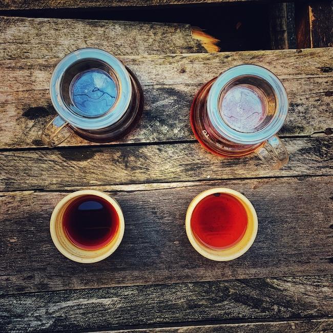 Auf einem Holzuntergrund stehen zwei gläserne Kannen und zwei Tontassen. Die linke Kombination ist mit Kaffee gefüllt, die rechte mit Tee - hier Cascara. Ein warmes Kaffee verbindet Menschen, genau wie Tee.
